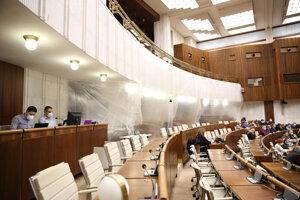 Pozitívni poslanci či poslanci z karantény boliv rokovacej sále oddelení fóliou.