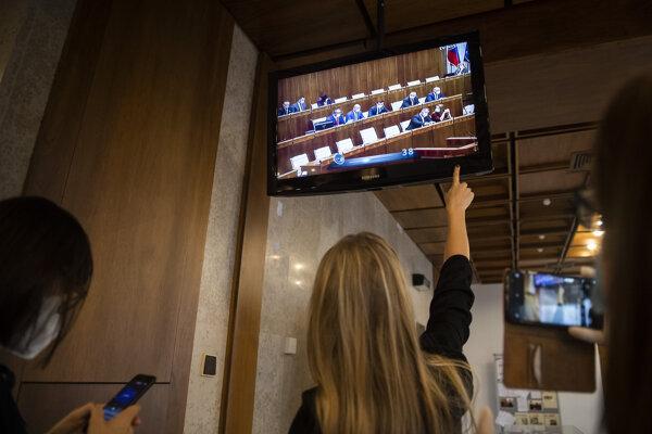 Televízna obrazovka na prízemí Národnej rady , na ktorej sledujú novinári mimoriadnu schôdzu k novele ústavného zákona o bezpečnosti štátu, dňa 28. decembra 2020. V rokovacej sále bol počas schôdze fóliou oddelený priestor pre poslancov s potvrdeným ochorením COVID-19, ale aj pre poslancov z karantény.