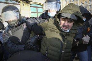 Policajti zatýkajú muža počas protestu proti väzneniu ruského opozičného lídra Alexeja Navaľného v Omsku.