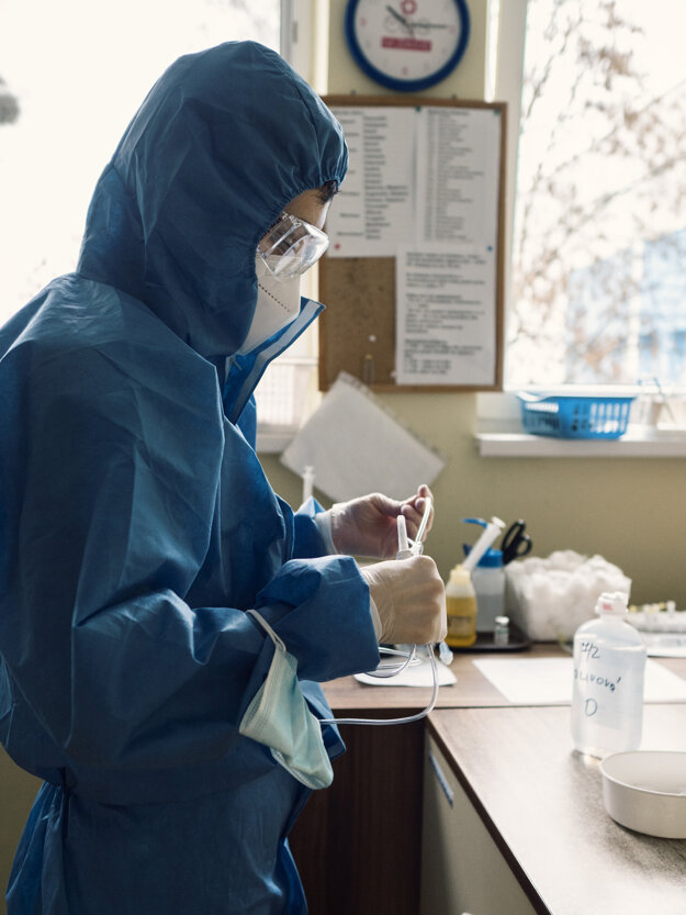 Zdravotníčka pripravuje roztok na infúznu terapiu pre pacientov s ochorením COVID-19.