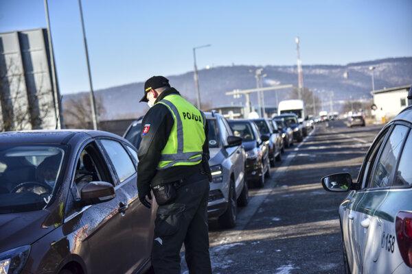 Policajt vykonáva hraničnú kontrolu pri vstupe na Slovensko