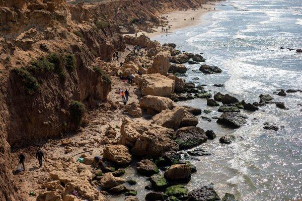 Ľudia čistia znečistené pobrežie.