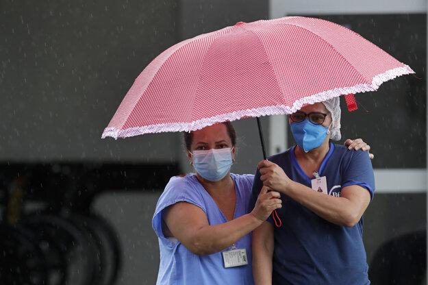 Brazílske zdravotné sestry v daždi sledujú, ako pacienta s podozrením na Covid-19 odváža sanitka do nemocnice v hlavnom meste. Brazília hlási rekordný počet úmrtí súvisiacich s novým koronavírusom za jediný deň.