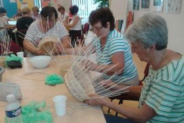 Ručné práce v dielňach v KOS počas leta zaujali. Na snímke ženy pletú košíky z pedigu.