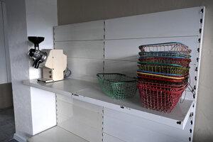 Na snímke expozícia obchodu približuje zariadenie vtedajšej predajne s potravinami. Vľavo prístroj na mletie kávy a vpravo nákupné košíky.