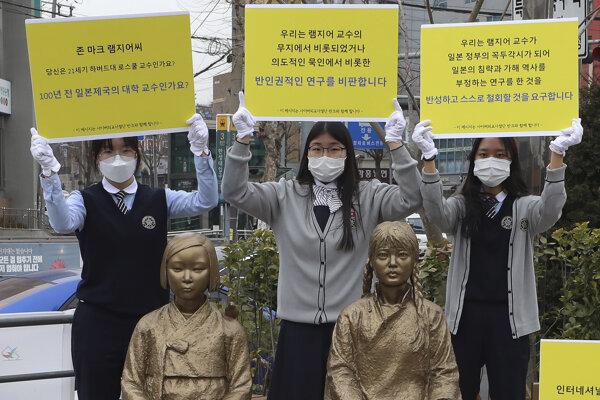 Študentky držia transparenty na protest proti nedávnej akademickej práce profesora Harvardovej univerzity J. Marka Ramseyera za sochami symbolizujúcimi vojnové sexuálne otrokyne v juhokórejskom Soule.