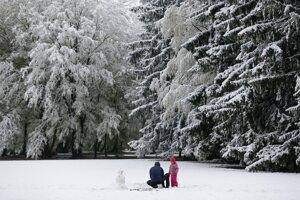 Muž so svojím dieťaťom stavajú snehuliaka v zasneženom parku v Záhrebe.