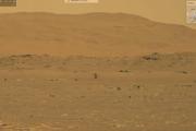 Záberu letu Ingenuity z rovera Perseverance. Helikoptéru môžete vidieť v strede záberu, ako sa vznáša nad povrchom Marsu.