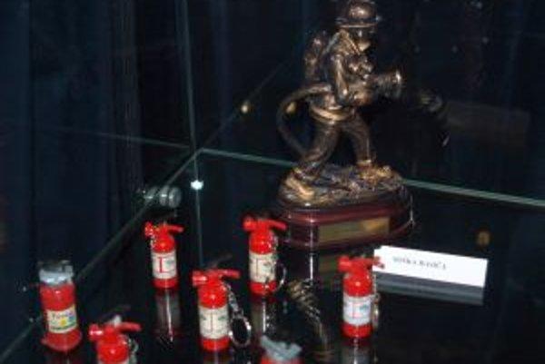 Soška hasiča a prívesky v tvare prenosných hasiacich prístrojov.