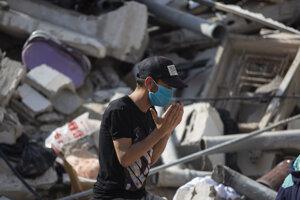 Izraelské nálety v Gaze si už vyžiadali takmer 200 obetí. Na snímke sa Palestínčan modlí za obete na troskách jednej z budov.