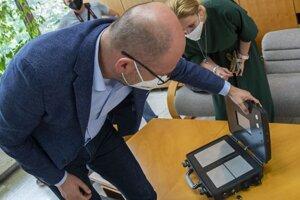 Richard Sulík si prezerá prototyp prístroja od nemenovaného slovenského vynálezcu na zisťovanie ochorenia na Covid 19.
