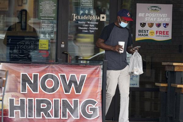 """Zákazník s ochranným rúškom sa pozerá do mobilného telefónu a kráča okolo nápisu """"Na prenájom"""" po vyzdvihnutí objednávky z reštaurácie v texaskom meste Richardson."""