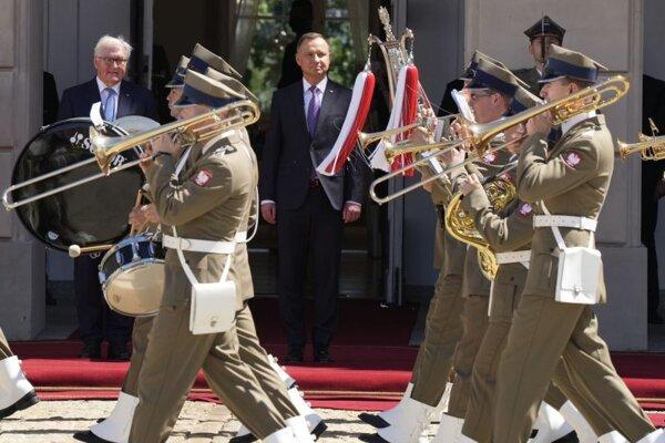 Nemecký prezident Frank-Walter Steinmeier (vľavo) a poľský prezident Andrzej Duda sledujú uvítací ceremoniál vo Varšave.