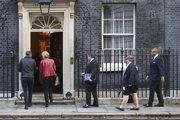 Britský ministri prichádzajú na rokovanie vlády na Downing Street.