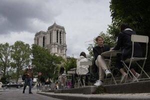 Ľudia sedia na terase reštaurácie pred katedrálou Notre-Dame v Paríži vo štvrtok 20. mája 2021.