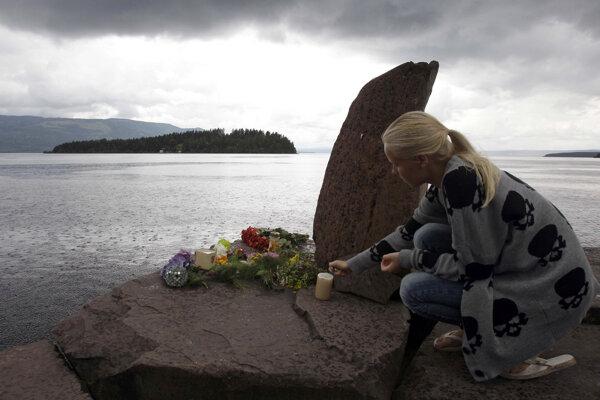 Na archívnej snímke z 24. júla 2011 žena zapaľuje sviečku na pamiatku obetí júlovej masakry na nórskom ostrove Utöya. Bol to najhorší útok jednotlivca v dejinách Nórska.