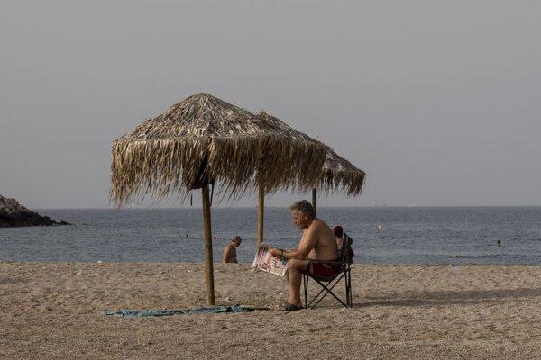 Muž číta noviny na pláži na predmestí Atén v Glyfade 23. júna 2021. Teploty v Grécku sa v týchto dňoch presahujú 40 stupňov Celzia.