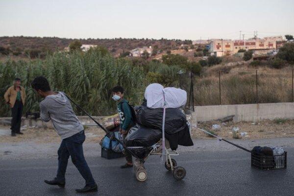 Migrant ťahá vozík s osobnými vecami po ceste na gréckom ostrove Lesbos.