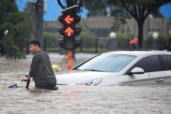 Muž s bicyklom sa brodí po zaplavenej ulici v čínskom meste Čeng-čou 21. júla 2021.