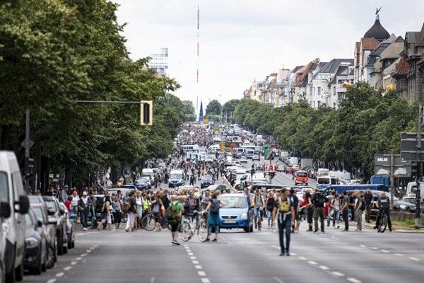 Skupina demonštrantov kráča po berlínskej ulici Bismarckstrasse.