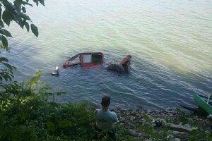 Traktor sa z vody snažia vytiahnuť ťažkou technikou.