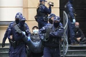 Policajti odnášajú demonštranta spred budovy Ústavného súdu vo Varšave.