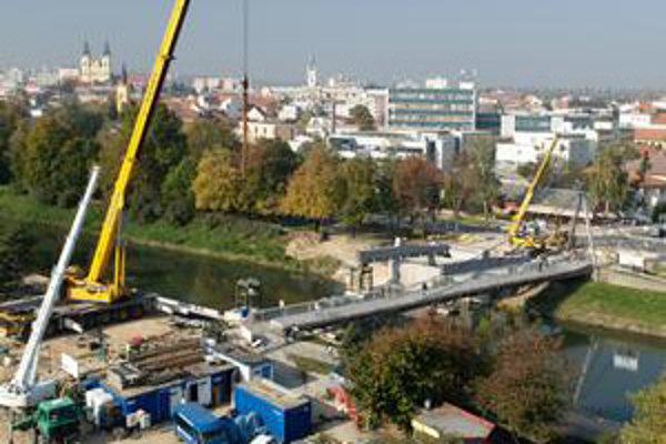 Ťažké stroje budujú nad riekou most, ktorý má odľahčiť dopravu v Nitre.