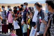 Afganskí utečenci s ochrannými rúškami nastupujú do lietadla pred ich odletom do Portugalska na medzinárodnom letisku v Aténach 28. septembra 2021.