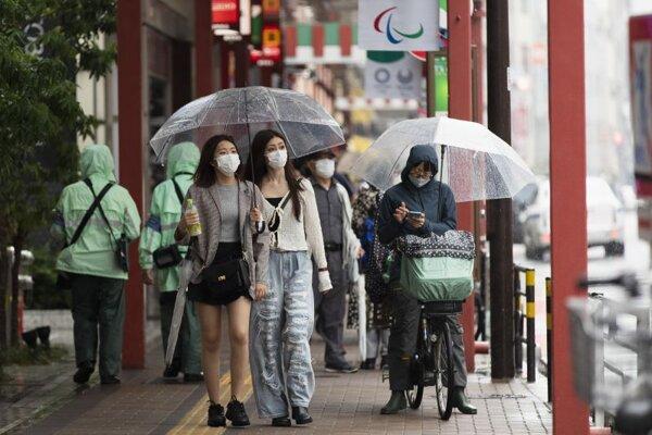 Ľudia s ochrannými rúškami prechádzajú po známej nákupnej oblasti Asakusa v japonskom Tokiu.