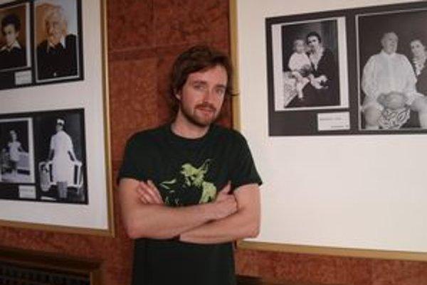 Juraj Hrčka s fotografiami svojich kolegov. Výstava je vo foyer Divadla Andreja Bagara.