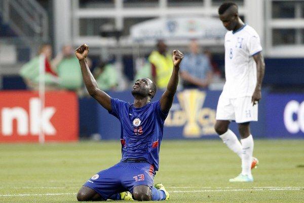 Futbalista Haiti Kevin LeFrance (vľavo) sa teší z víťazstva a postupu zo skupiny, vpravo kráča sklamaný hráč Hondurasu Rubillo Castillo.