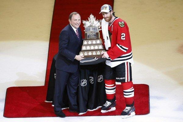 Duncan Keith (vpravo) preberá od komisára NHL Garyho Bettmana Conn Smythe Trophy pre najužitočnejšieho hráča play-off.