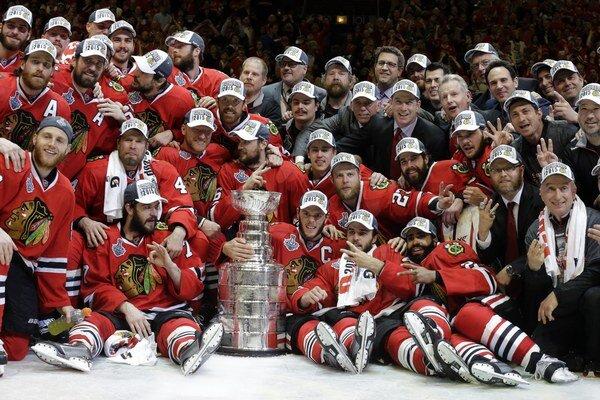 Hokejisti Chicaga Blackhawks pózujú s víťaznou trofejou.