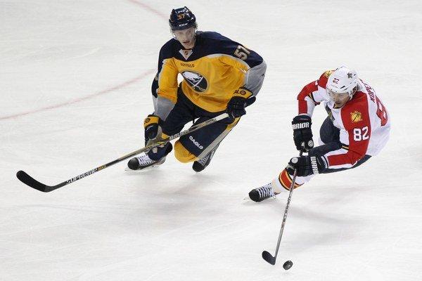 Tomáš Kopecký (vpravo) sa snaží udržať puk na hokejke pred hráčom Buffala Tylerom Myersom.