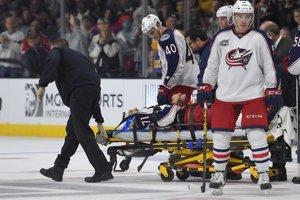 Hokejistu Columbusu Nicka Foligna odnášajú z ľadu na nosidlách po  zranení, ktoré utrpel v tretej tretine zápasu Los Angeles Kings - Columbus Blue Jackets v Los Angeles 26. októbra 2014. Vpravo v popredí Slovák Marko Daňo