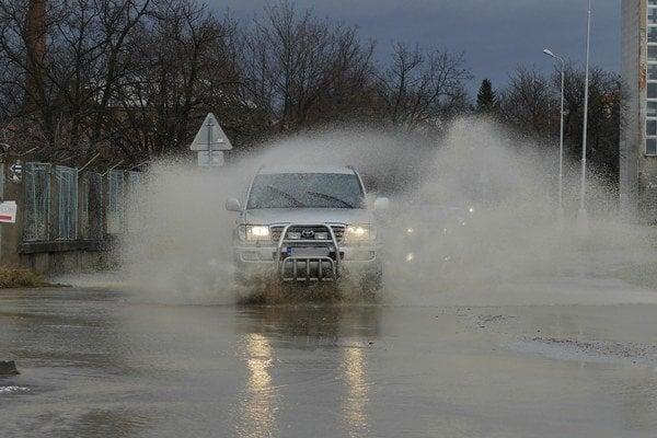 Auto rozstrekuje vodu po zaliatej ceste v Pezinku.