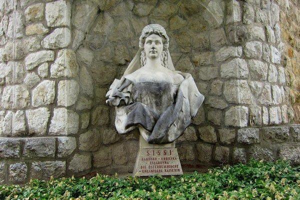 Socha Alžbety Bavorskej stojí pri stene kúpeľného domu Irma.