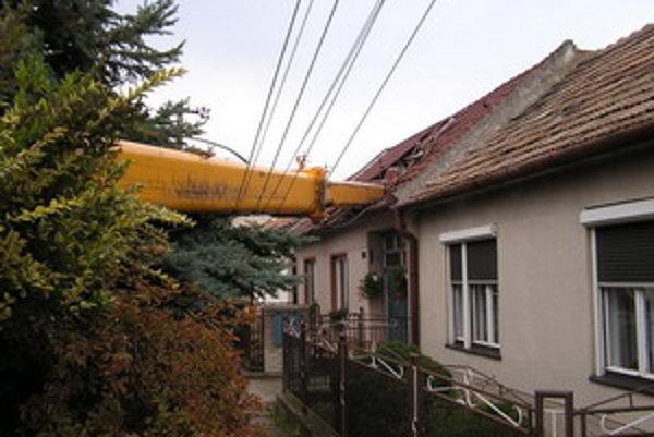 Prevrátený žeriav. Jeho vysunuté rameno zasiahlo strechu domu.