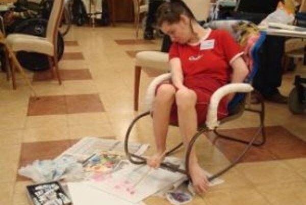 Ilustračné foto. Danka Pekarovičová maľuje nohami sediac na špeciálne upravenom kresle.