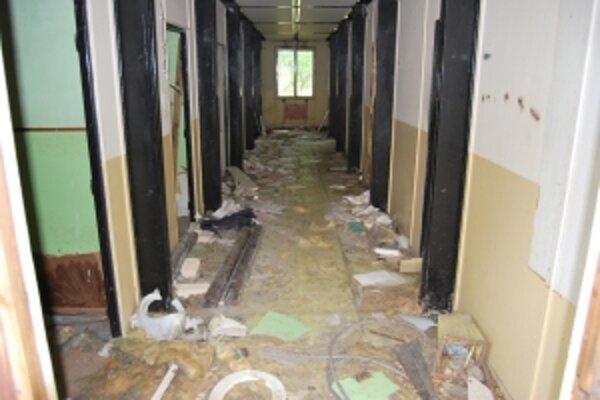 Hlavná chodba ubytovne je zahádzaná zničeným majetkom a odpadkami.