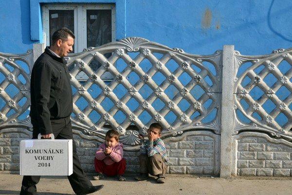 Člen okrskovej volebnej komisie s prenosnou volebnou schránkou v rómskej osade v Trebišove.
