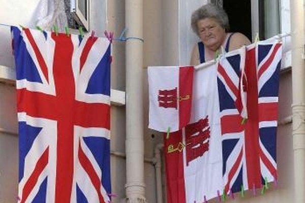 Žena sa pozerá z okna na oslavy tristého výročia britskej zvrchovanosti nad Gibraltárom.