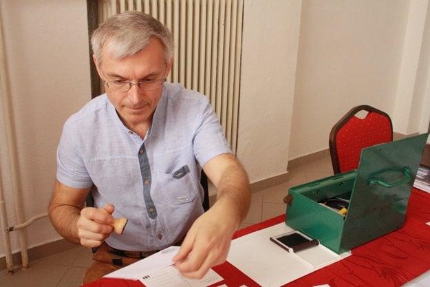 Handlovský mestský poslanec a filatelista Michal Hertlík pečiatkuje karty.