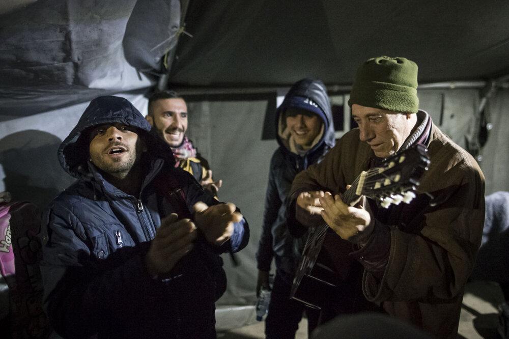 Utečenci si hrajú na gitaru.
