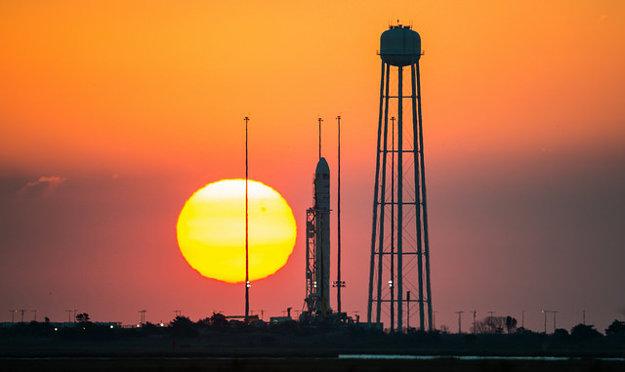 Raketa Antares s kozmickou loďou Cygnus na rampe vo Virgínii pri východe Slnka.