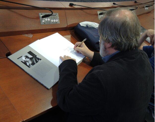 Autor pri podpisovaní svojej knihy.