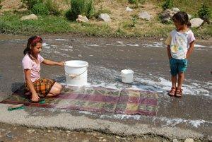 Letný obraz na vidieku. Deti čistia koberce, ktoré potom rodina suší niekoľko dní na plotoch.