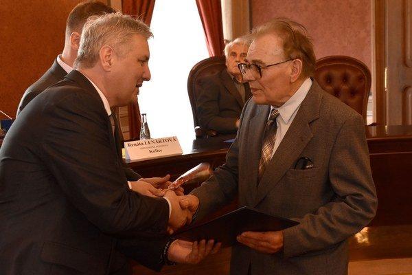 Vpravo politický väzeň Ján Grega si preberá dekrét z rúk predsedu ÚPN Ondreja Krajňáka (vľavo).