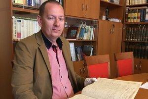 Richard Pavlovič. Riaditeľ Štátneho archívu v Košiciach ukazuje kongregačnú zápisnicu Abovskej župy z rokov 1564 – 1570.
