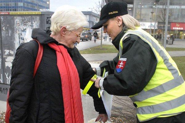 Reflexná páska môže zachrániť život. Krajská policajná hovorkyňa Jana Mésarová dôchodcom ukazuje, ako mať správne pásku zapnutú.
